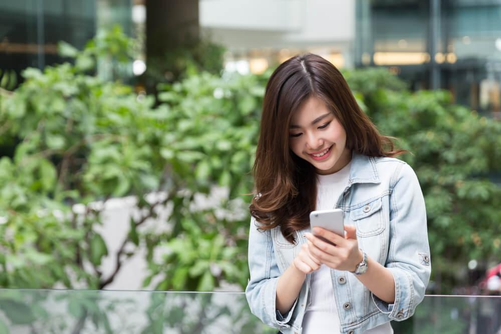 スマートフォンを見て微笑む女性