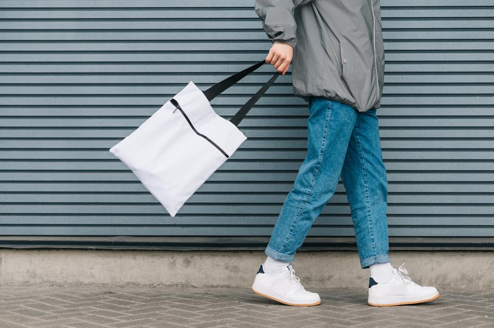 白いトートバッグを持って歩く男性