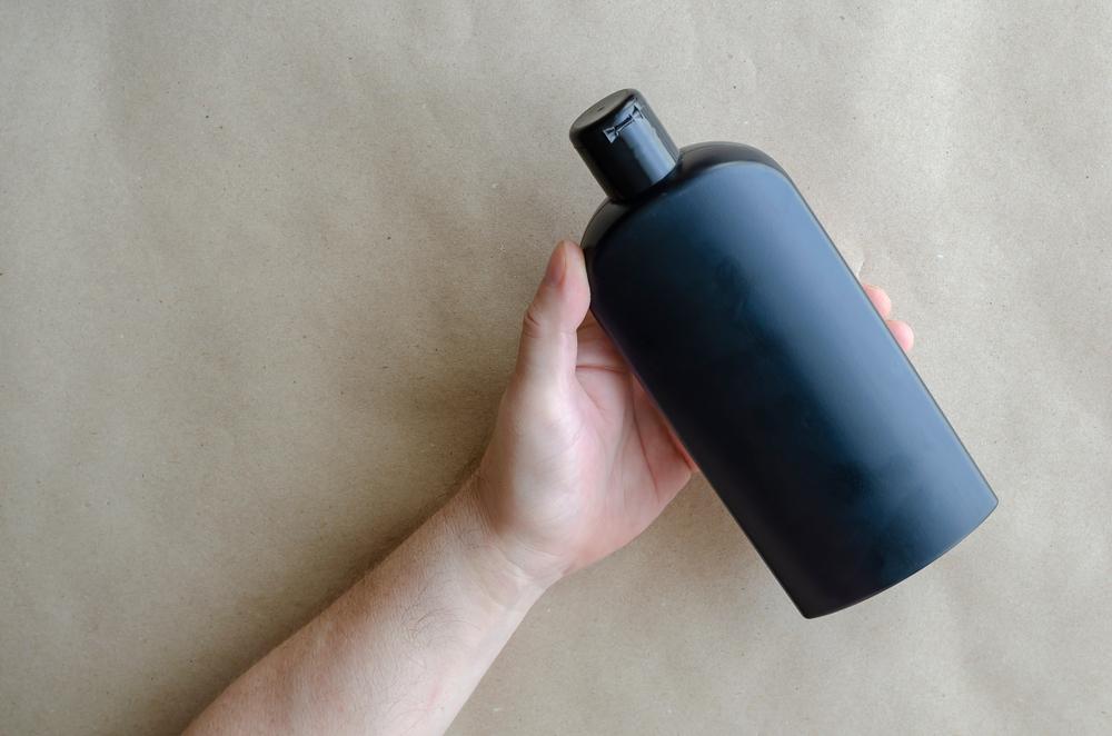 黒ボトルのボディソープを持つ男性