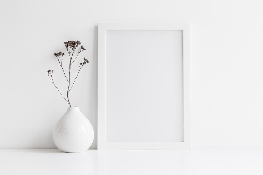 白い壁の前の白花瓶と白額縁