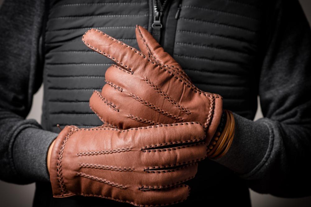 茶色い手袋をはめた男性