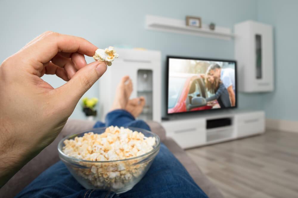 ポップコーンを食べながら映画を見る男性