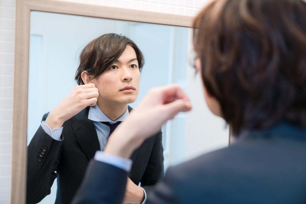 鏡を見ながら髪をいじる男性