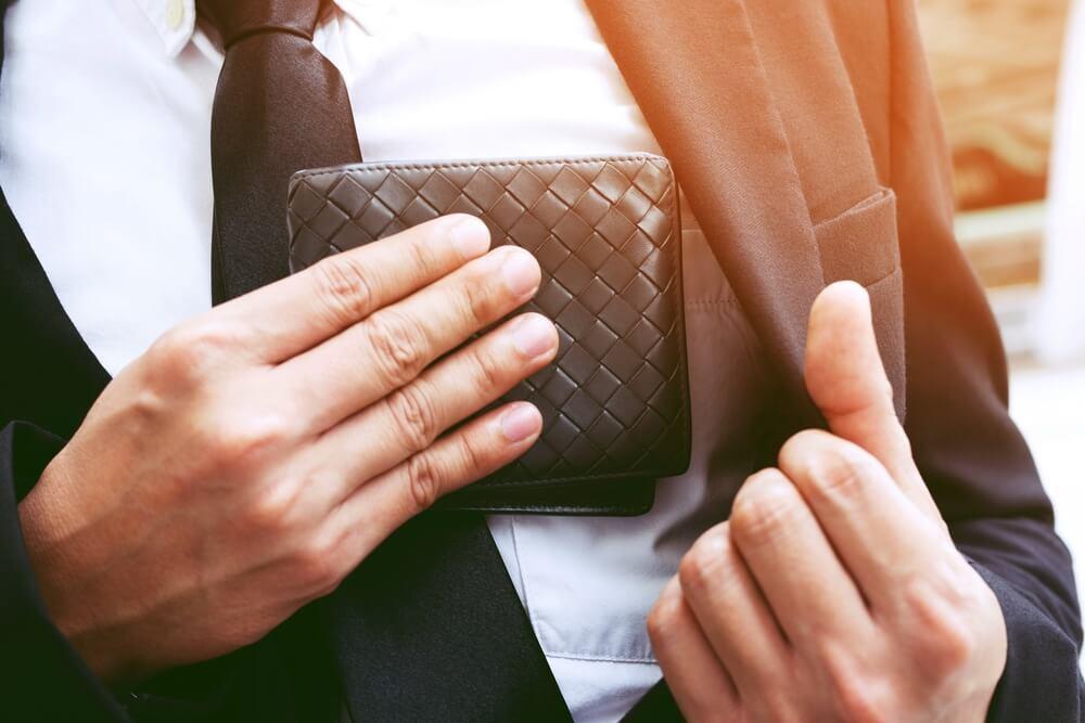 財布をポケットに入れる男性