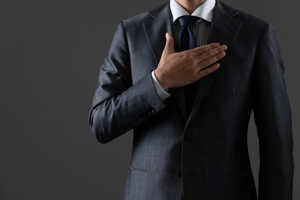 胸に手を当てるスーツ姿の男性
