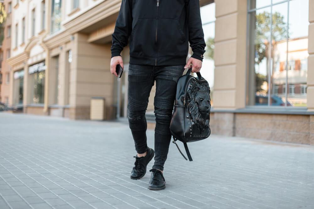 黒のリュックを持ち歩く男性