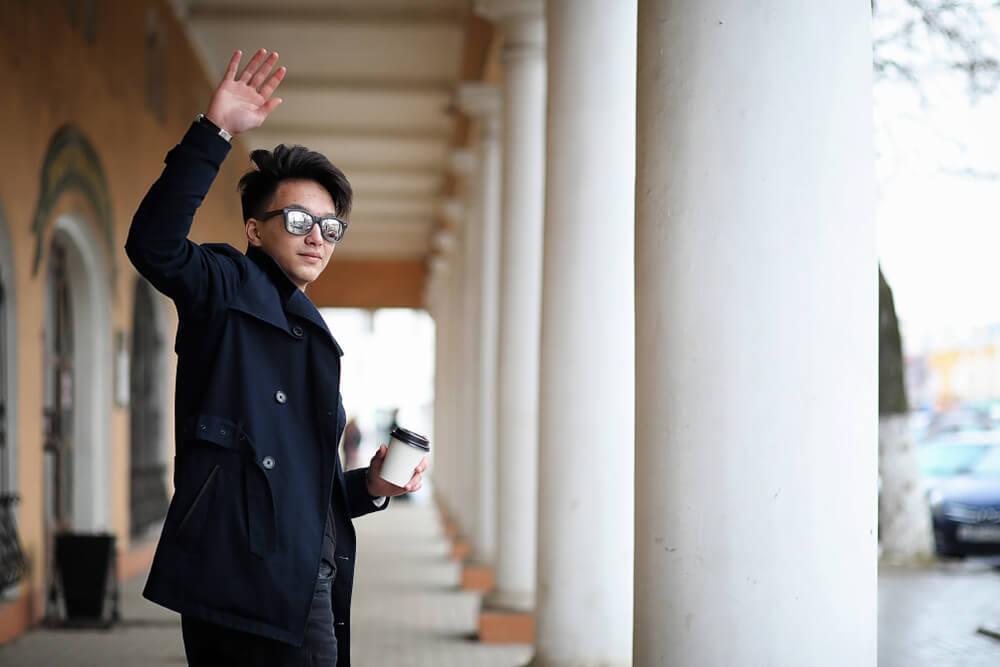 サングラスをかけて手を上げる男性