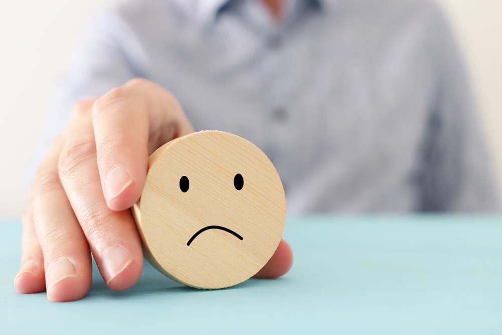 悲しい顔をした積み木を持つ男性