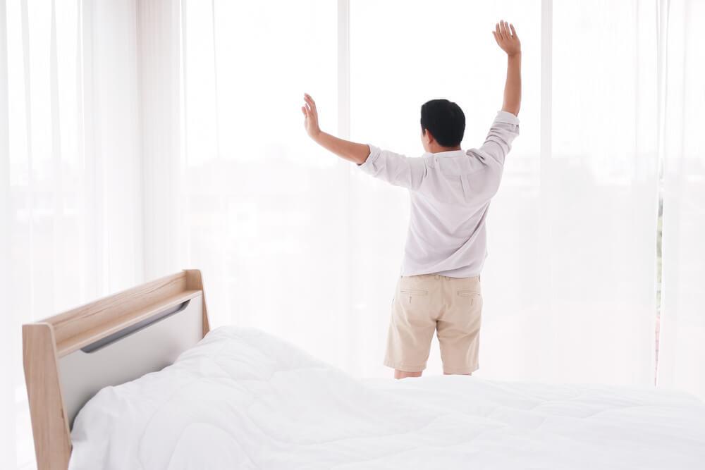 窓辺で両手を上げる男性