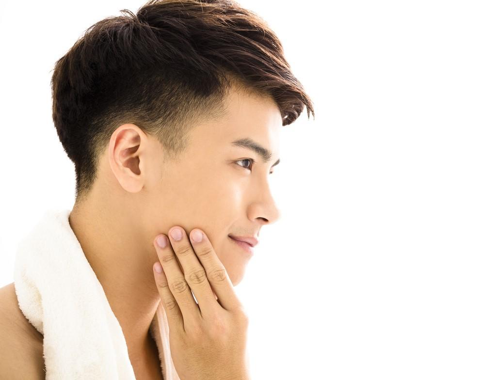 洗顔後の肌をチェックする男性