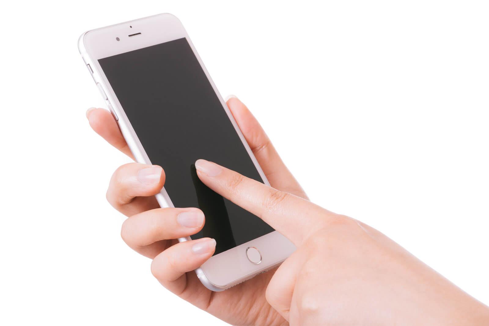 格安スマホの「エックスモバイル」のiPhoneを触る手