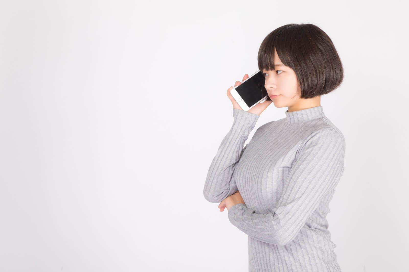 auでMNP(ナンバーポータビリティ)の予約番号を取得するために電話する女性