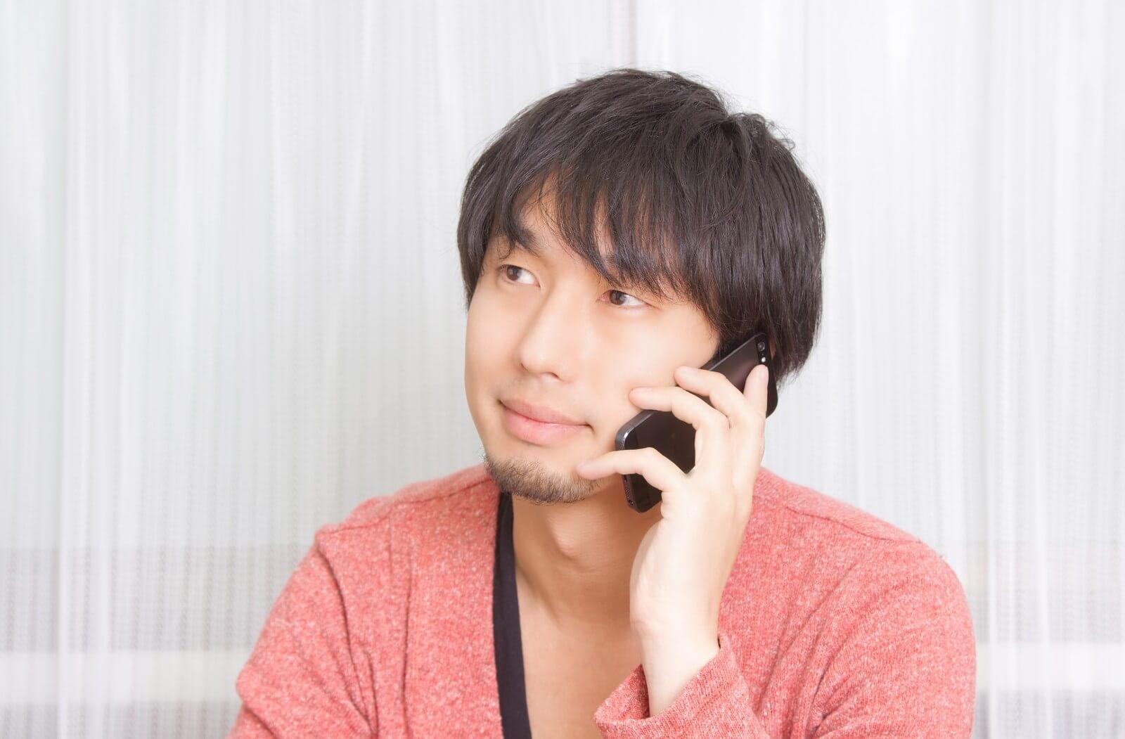 無制限の電話かけ放題プランを採用するエックスモバイルのスマホで電話する男性