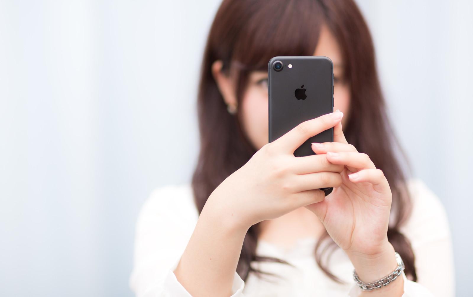 iPhone 7の格安SIMを入れて必要な設定をする女性