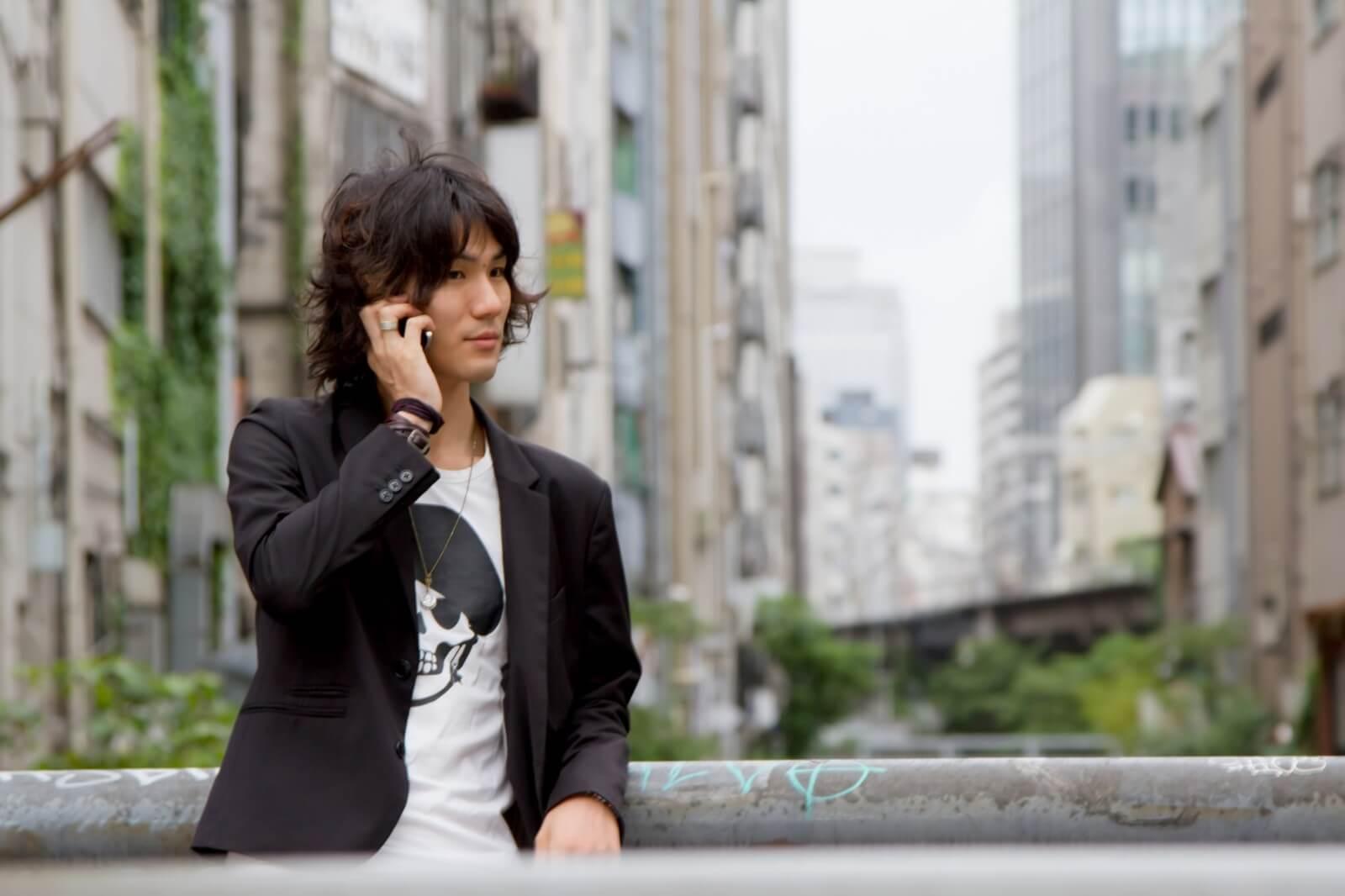 エックスモバイルの格安スマホで電話をする男性