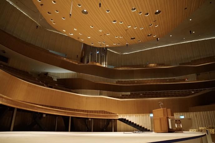 天井部分に設置されている穴の空いた板は、その日の動員数によって昇降するように設計。これは建築音響工学に基づいて、音響を均等にするための工夫だという。