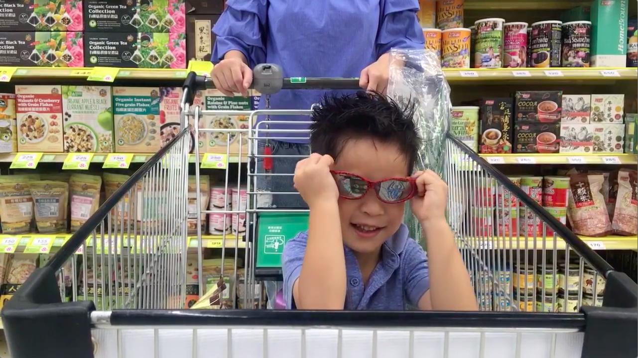 一個小孩坐在購物車裡戴著墨鏡好神氣