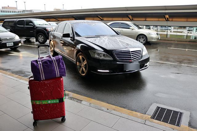 一台車和一個行李在機場外