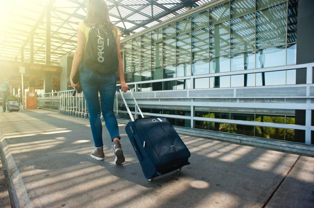 一位背著背包拉著行李的旅客正要走進機場航廈