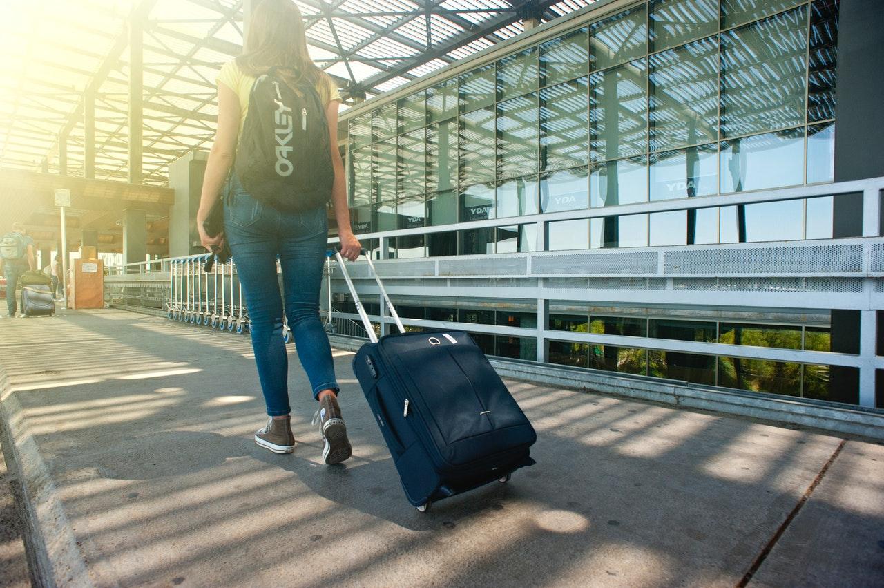 一名女子拖著行李走在機場外