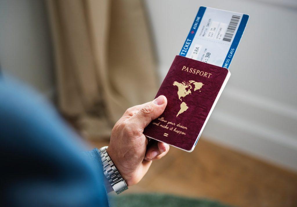 穿著藍西裝的商務人士拿著他的護照與登機證