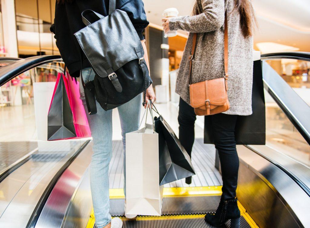 兩個人在電扶梯上提著大大小小的購物袋