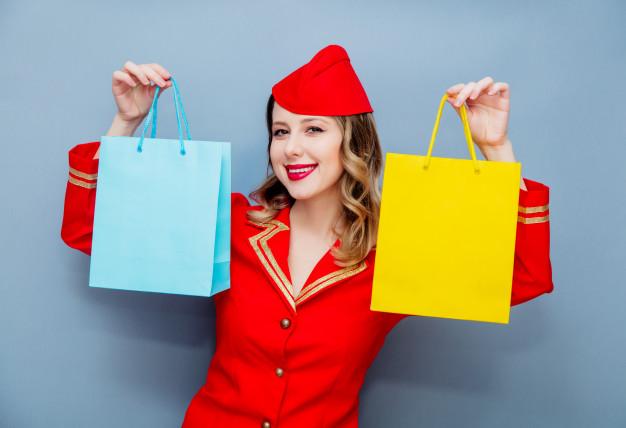 穿著紅色衣服的空姐,右手拿一個 tiffany 藍的紙袋,左手拿著一個黃色的紙袋