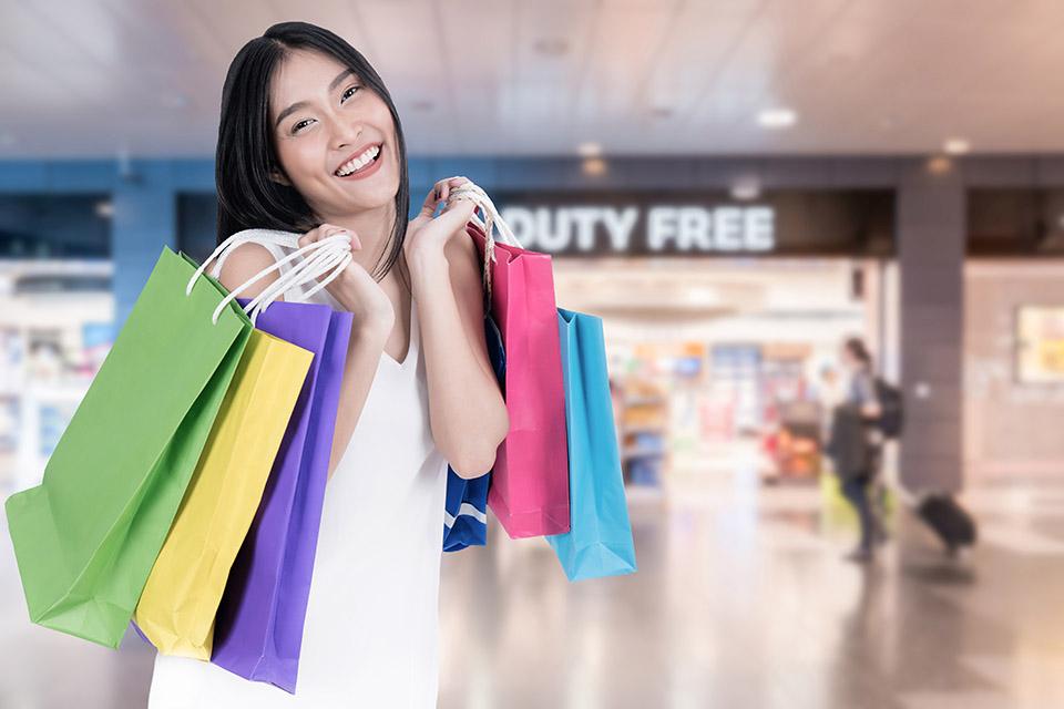 一個女人手拿著綠、黃、紫、粉紅和藍色的購物袋,站在免稅店前笑得很燦爛