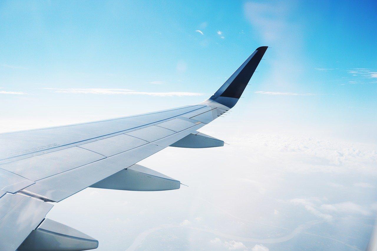 飛行常客計劃:飛機在高空中白色的雲與藍色的天