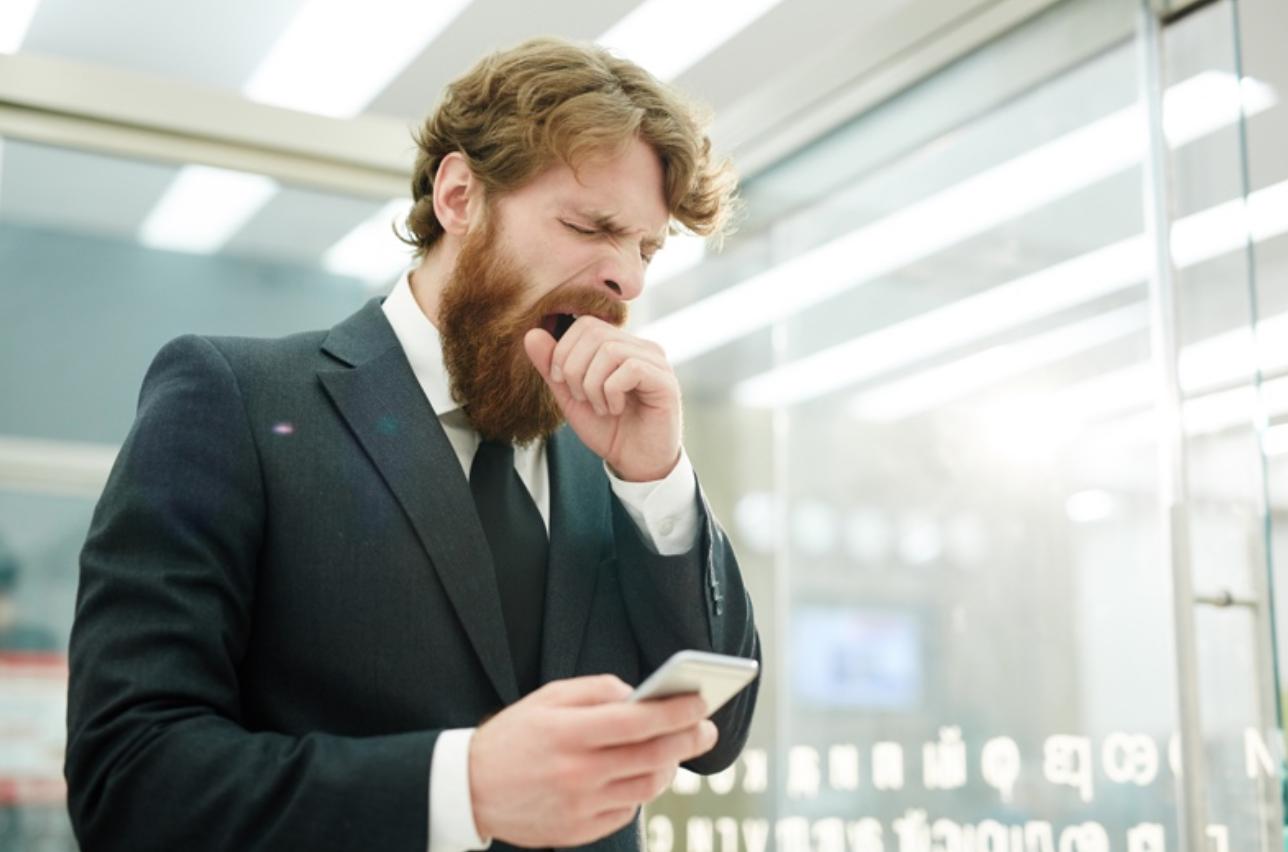 一名男子穿著西裝留著大鬍子在機場等待飛機打哈欠很累