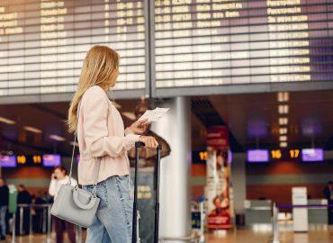 長頭髮的金髮女生背著背包在機場大廳看著機票