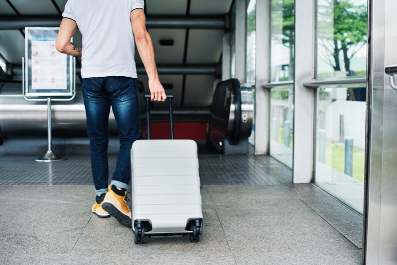 穿著白色襯衫搭配牛仔褲的男子拖著白色行李箱準備要出境出國去玩