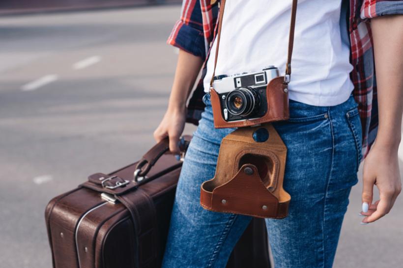 穿著白色衣服搭配牛仔褲的人出國手提行李加上相機揹在身上