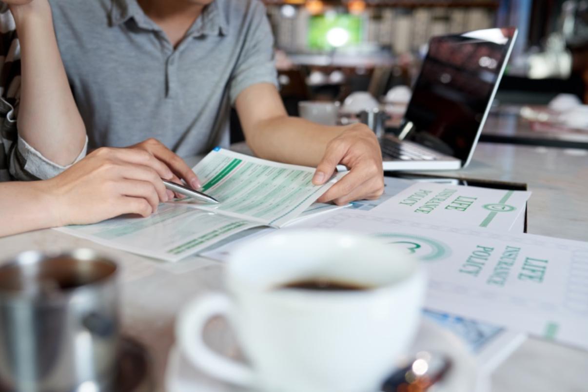 桌上擺滿紙張有杯咖啡在桌上兩人在討論保險