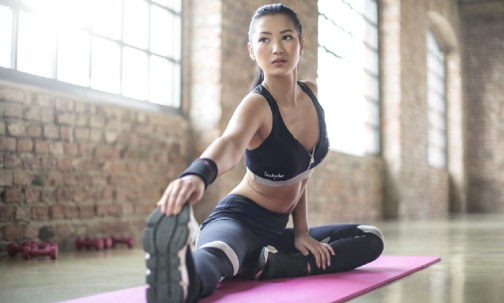 一名女生穿著黑色運動緊身衣在家做運動