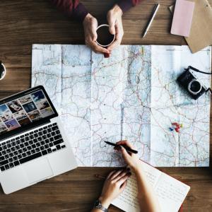 桌面上有地圖、筆電和相機,兩個人正在研究旅遊計畫