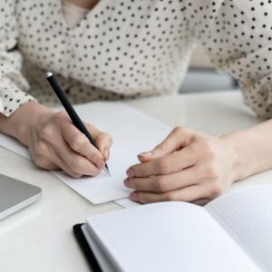 一個人手拿著筆在白紙上寫