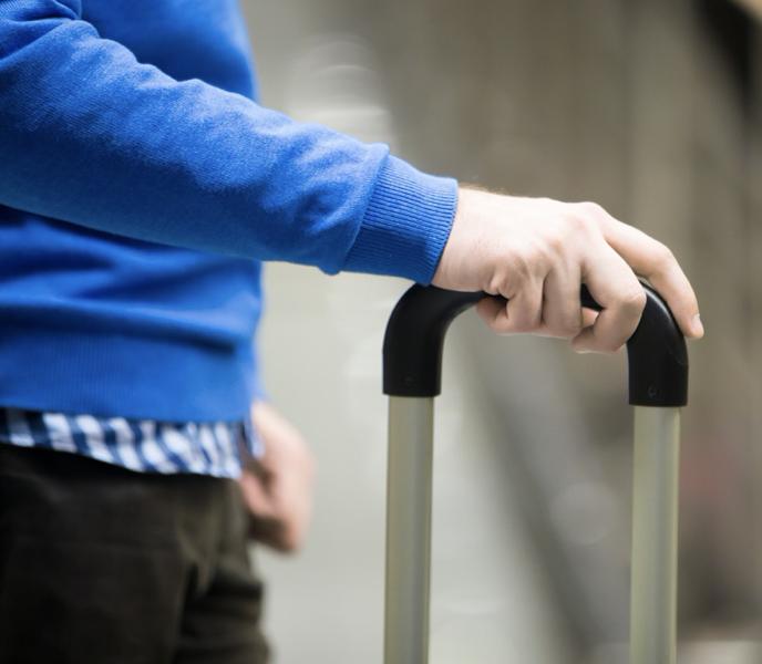 一個穿藍色毛衣的人手扶著行李箱桿子