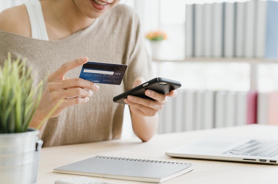 女子拿著手機跟信用卡再購買東西