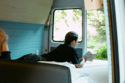 リアのベッドスペースの使い方は自由自在。陽の光を浴びての読書は縁側のようです。