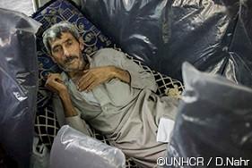 ムハンマド・アリは55歳の肺病を患う難民であり、トルコとイラクのクルディスタン地域の間の国境で、ガウィラン難民キャンプへと向かうバスの中に横たわっています。