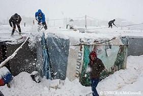 7日早朝、吹雪の中レバノンのベッカー高原の非公式テント居住地にあるシェルターの雪かきをするシリア難民。