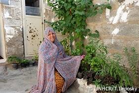 新しい水道システムのおかげで、サルヴェスタン難民キャンプの自宅で花や植物を育てられるようになったファルザネー