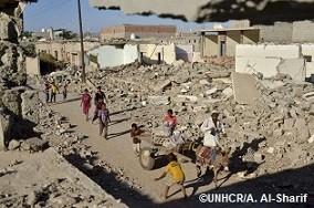 ジンジバルのアルオラ近郊で破壊された建物の間をろばの荷馬車が通る横で遊ぶ子どもたち。