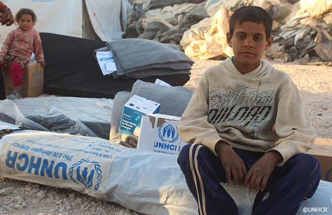 UNHCRが供給したマットの上に座るシリアの少年