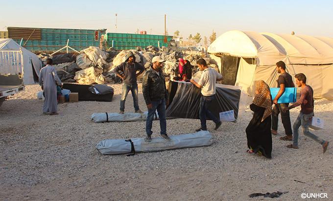 写真:支援物資を受け取るシリアの避難民