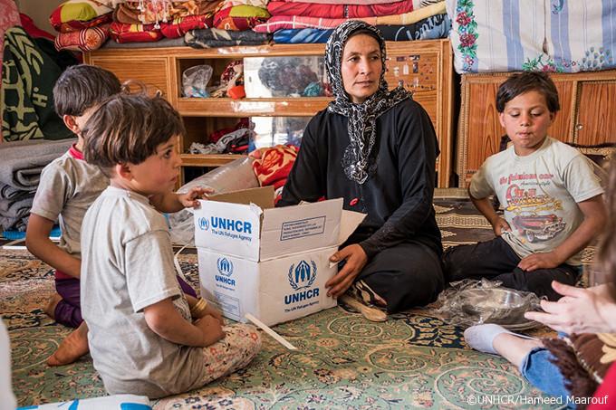 写真:救援物資の中身を見るファティマと子ども達