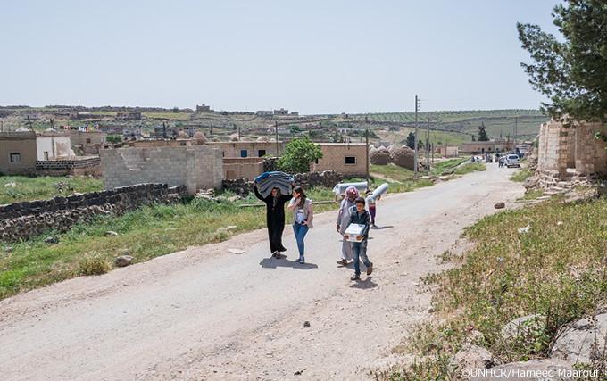 写真:救援物資を運ぶフセインとファティマ、UNHCRの職員