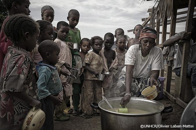 写真:調理をするアダマと、彼女の料理を待つ仲間の難民