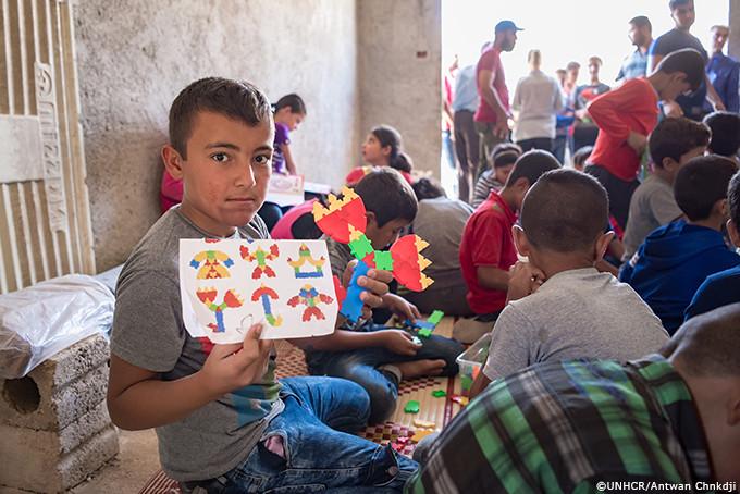 自分で工作した作品を見せてくれるシリアの少年
